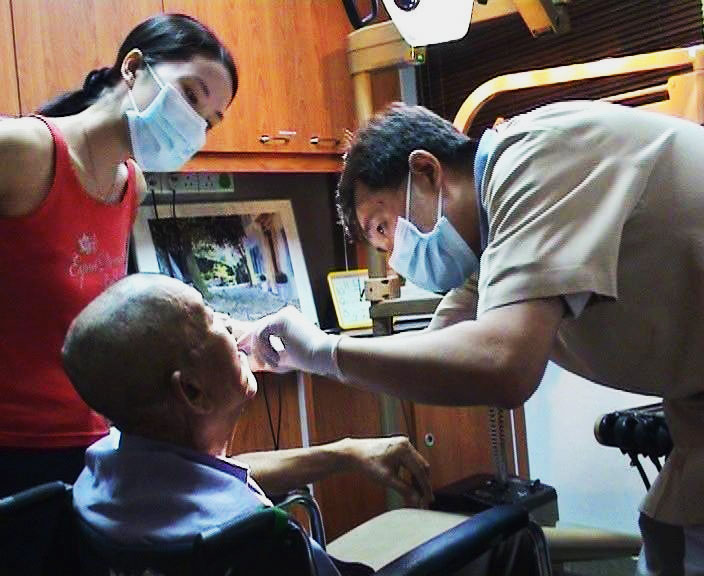 Dr Victor Lee helping the elderly with dental care.