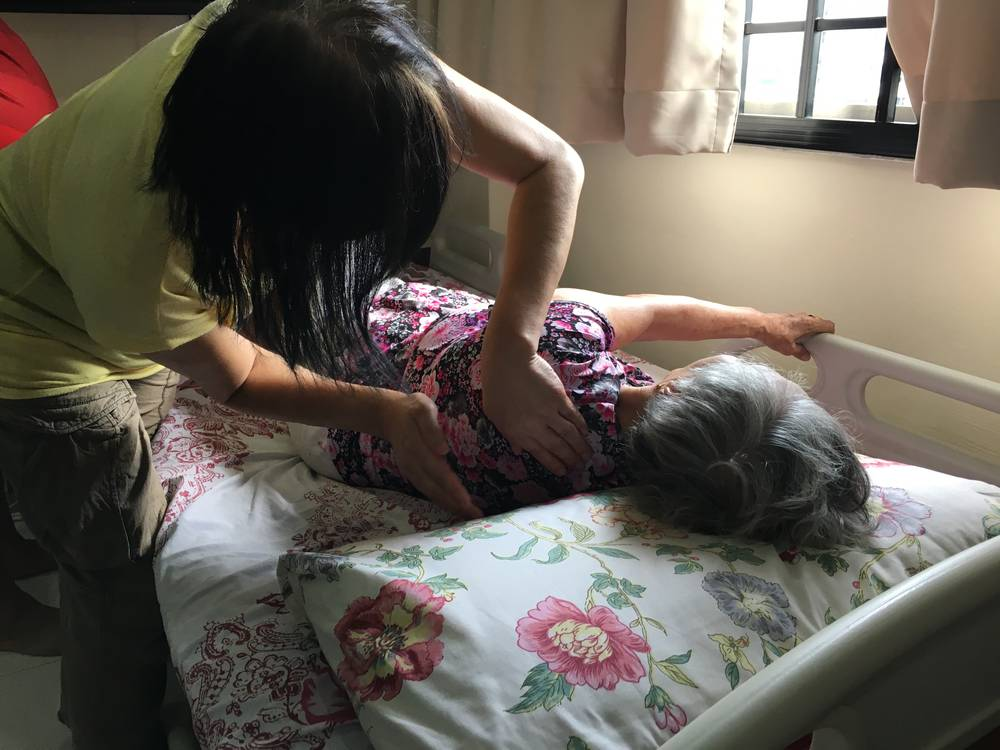 Ah Ma gets therapy from an elderly care provider to aid her recovery at home