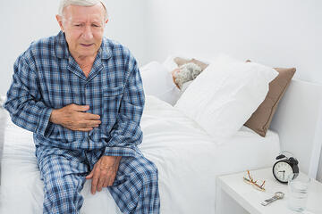 Elderly man suffering with belly pain in the bedroom