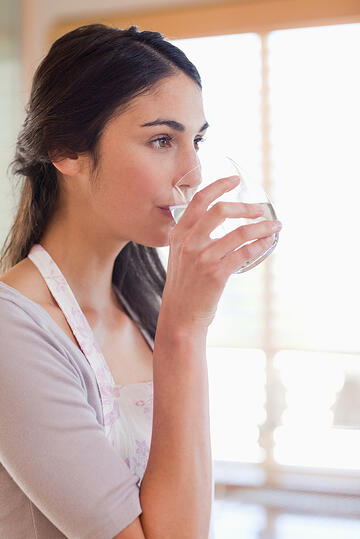Portrait of a woman drinking water in her kitchen-1