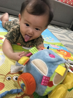 baby on playmat playing with a toy